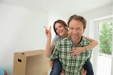 Woman piggyback man new house happy Stock Photo - Premium Royalty-Free, Code: 6121-07970098