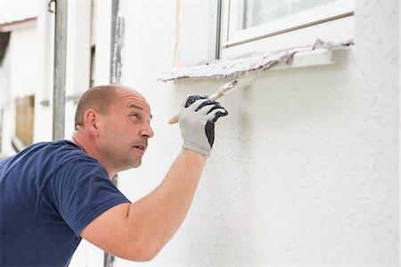 Man alone painting brush window wall house Stock Photo - Premium Royalty-Free, Code: 6121-07970027