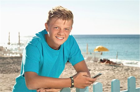 Teenager beach summer holiday fence mobile phone Stock Photo - Premium Royalty-Free, Code: 6121-07970188