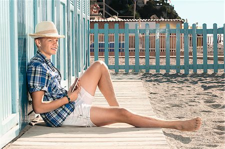 Boy beach summer holiday straw hat sitting Stock Photo - Premium Royalty-Free, Code: 6121-07970190