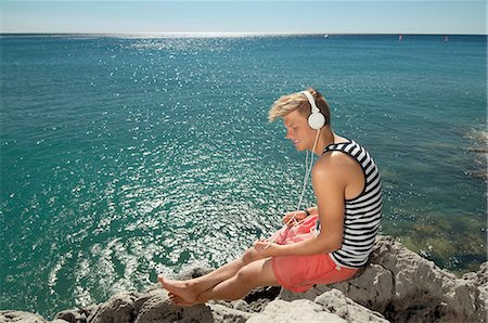 Teenager boy relaxing headphones listening music Stock Photo - Premium Royalty-Free, Code: 6121-07970195