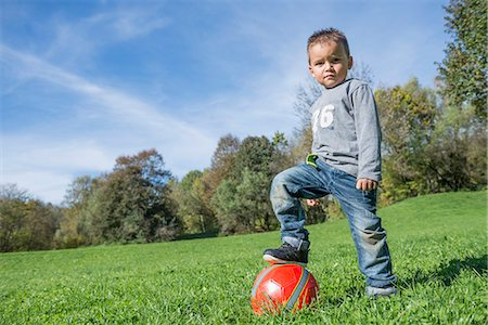 Portrait small boy stepping on red football meadow Stock Photo - Premium Royalty-Free, Code: 6121-07970113