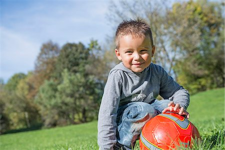 Portrait small boy red football meadow smiling Stock Photo - Premium Royalty-Free, Code: 6121-07970114