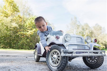 Portrait small boy checking tire model vintage car Stock Photo - Premium Royalty-Free, Code: 6121-07970119