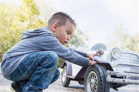 Boy checking wheel model toy vintage car Stock Photo - Premium Royalty-Free, Code: 6121-07970121
