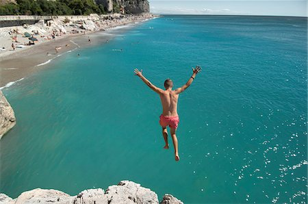 shirtless teen boy - Boy holiday jump water ocean risk teenager Stock Photo - Premium Royalty-Free, Code: 6121-07970203