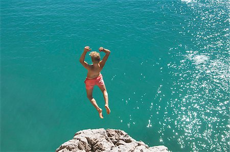 Teenager water cliff sunshine summer holiday jump Stock Photo - Premium Royalty-Free, Code: 6121-07970201