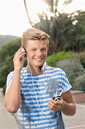 Portrait male teenager listening music MP3 player Stock Photo - Premium Royalty-Free, Code: 6121-07970205