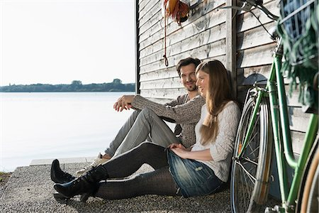 pair - Young couple sitting relaxing lake boathouse Stock Photo - Premium Royalty-Free, Code: 6121-07992549