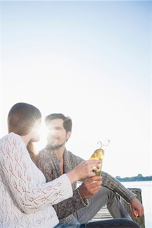 Young man woman sitting jetty drinking beer Stock Photo - Premium Royalty-Free, Code: 6121-07992550