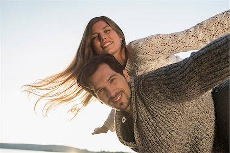 pair - Portrait man woman fun riding piggyback sunset Stock Photo - Premium Royalty-Free, Code: 6121-07992556