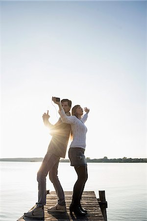 Young happy couple dancing jetty sunset Stock Photo - Premium Royalty-Free, Code: 6121-07992563