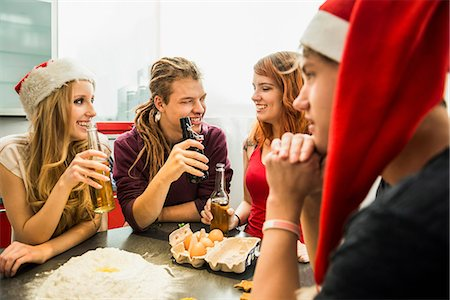 Group of friends preparing cake and drinking beer on Christmas Eve, Munich, Bavaria, Germany Stock Photo - Premium Royalty-Free, Code: 6121-07992582