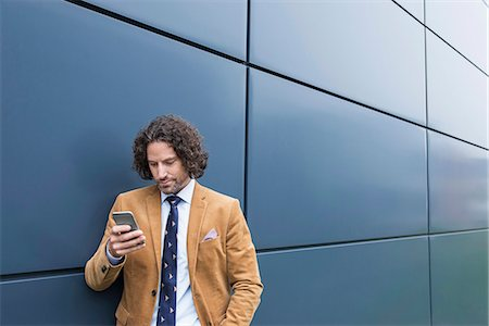 Man business suit cell phone reading SMS Stock Photo - Premium Royalty-Free, Code: 6121-07992503