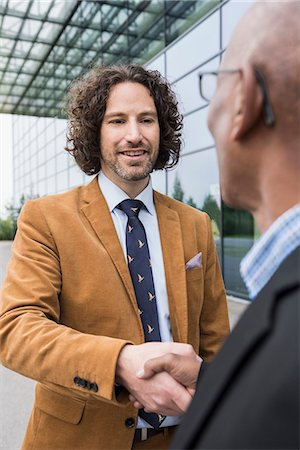 Close up portrait men shaking hands multiracial Stock Photo - Premium Royalty-Free, Code: 6121-07992510