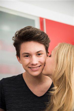 Young woman kissing man cheek, Munich, Bavaria, Germany Stock Photo - Premium Royalty-Free, Code: 6121-07992515