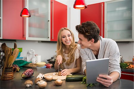 Young couple preparing food in kitchen, Munich, Bavaria, Germany Stock Photo - Premium Royalty-Free, Code: 6121-07992516