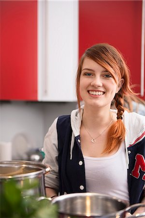Young woman cooking in the kitchen, Munich, Bavaria, Germany Stock Photo - Premium Royalty-Free, Code: 6121-07992527