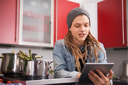 Young man looking at recipe on digital tablet, Munich, Bavaria, Germany Stock Photo - Premium Royalty-Free, Code: 6121-07992529