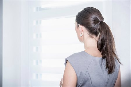 Rear view of a businesswoman looking out office window, Munich, Bavaria, Germany Stock Photo - Premium Royalty-Free, Code: 6121-07992533