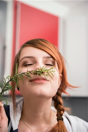 Woman smelling a twig of rosemary, Munich, Bavaria, Germany Stock Photo - Premium Royalty-Free, Code: 6121-07992532