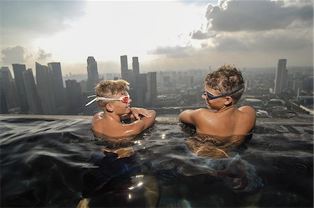 Teenage boys in an infinity pool, Marina Bay Sands, Singapore City, Singapore Stock Photo - Premium Royalty-Free, Code: 6121-07992641