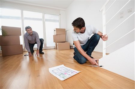 Father and son measuring wooden floor in new home, Bavaria, Germany Stock Photo - Premium Royalty-Free, Code: 6121-07992655