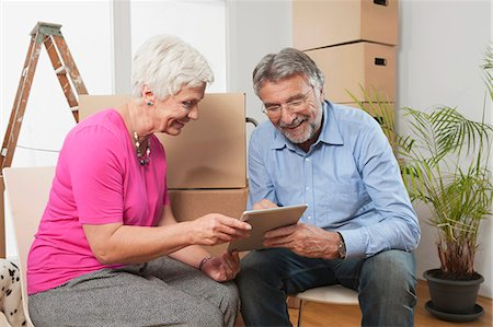 Senior couple using a digital tablet in new apartment, Bavaria, Germany Stock Photo - Premium Royalty-Free, Code: 6121-07992658