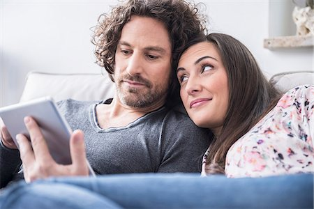 Couple using a digital tablet at home, Munich, Bavaria, Germany Stock Photo - Premium Royalty-Free, Code: 6121-07992607