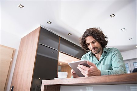 flat - Man using a digital tablet in a kitchen, Munich, Bavaria, Germany Stock Photo - Premium Royalty-Free, Code: 6121-07992613
