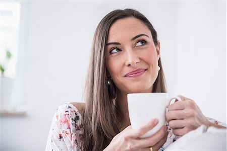 Beautiful woman drinking cup of coffee at sofa, Munich, Bavaria, Germany Stock Photo - Premium Royalty-Free, Code: 6121-07992610