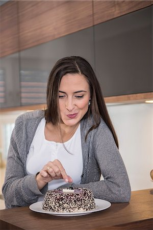 delicious - Woman eating cake in a kitchen, Munich, Bavaria, Germany Stock Photo - Premium Royalty-Free, Code: 6121-07992614
