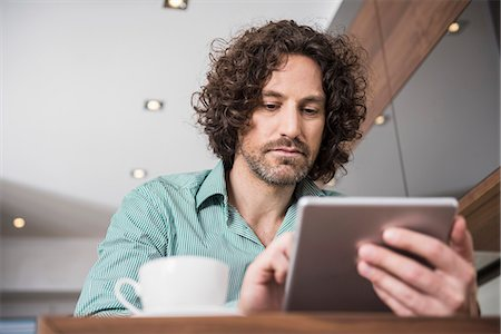 Man using a digital tablet in a kitchen, Munich, Bavaria, Germany Stock Photo - Premium Royalty-Free, Code: 6121-07992615