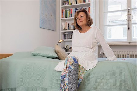 Senior woman sitting on bed and dreaming, Munich, Bavaria, Germany Stock Photo - Premium Royalty-Free, Code: 6121-08106567
