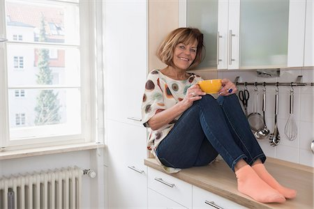 Happy senior woman sitting on kitchen slab and drinking tea, Munich, Bavaria, Germany Stock Photo - Premium Royalty-Free, Code: 6121-08106581