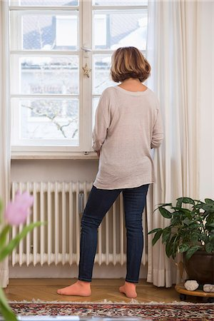 Rear view of senior woman looking through a window, Munich, Bavaria, Germany Stock Photo - Premium Royalty-Free, Code: 6121-08106590