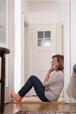 Profile shot of senior woman talking on mobile phone at doorway, Munich, Bavaria, Germany Stock Photo - Premium Royalty-Free, Code: 6121-08106595