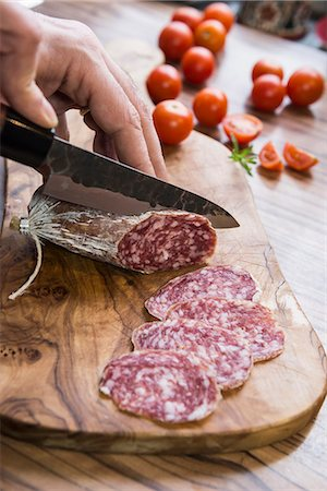 Person's hand chopping sausage with knife, Germany Stock Photo - Premium Royalty-Free, Code: 6121-08106535