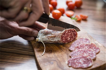 Person's hand chopping sausage with knife, Germany Stock Photo - Premium Royalty-Free, Code: 6121-08106536