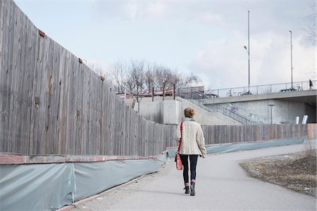 Rear view of a young woman walking along construction site fence on road, Munich, Bavaria, Germany Stock Photo - Premium Royalty-Free, Code: 6121-08106613