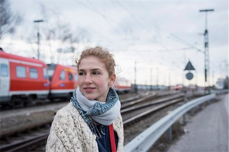 Portrait of a young woman with railway track and red train in the background, Munich, Bavaria, Germany Stock Photo - Premium Royalty-Free, Code: 6121-08106621