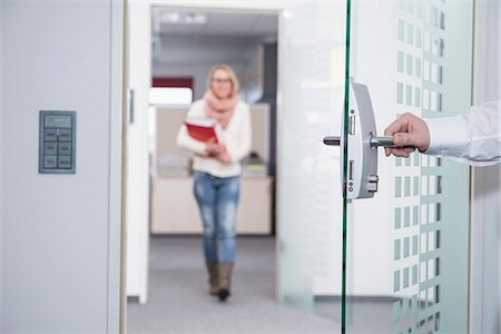 Businessman opening office door for his colleague, Munich, Bavaria, Germany Stock Photo - Premium Royalty-Free, Code: 6121-08106751
