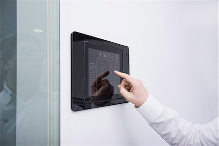 fingers holding - Man operating control panel on wall mounted, Munich, Bavaria, Germany Stock Photo - Premium Royalty-Free, Code: 6121-08106756