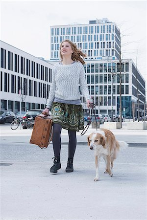 Young woman walking on road with dog and suitcase, Munich, Bavaria, Germany Stock Photo - Premium Royalty-Free, Code: 6121-08106736