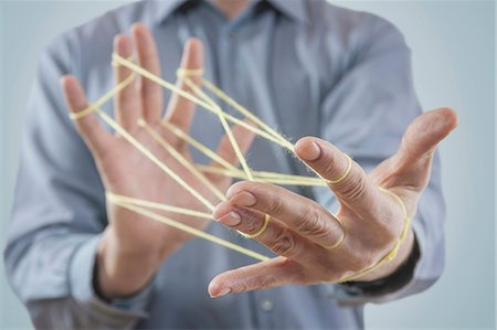 Mid section view of a man's hands making a cats cradle with string, Bavaria, Germany Stock Photo - Premium Royalty-Free, Code: 6121-08106840