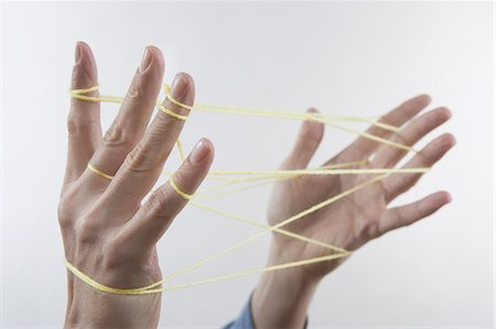 string - Close-up of a man's hands making a cats cradle with string, Bavaria, Germany Stock Photo - Premium Royalty-Free, Code: 6121-08106841