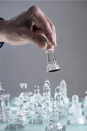 Close-up of man's hand going for checkmate while playing chess, Bavaria, Germany Stock Photo - Premium Royalty-Free, Code: 6121-08106845