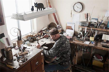 Senior male jeweler hitting punches in workshop, Bavaria, Germany Stock Photo - Premium Royalty-Free, Code: 6121-08106899