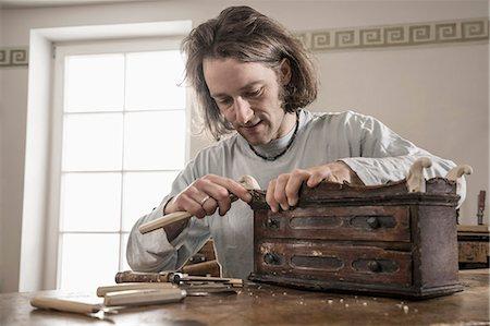 Carpenter carving on an antique bone box at workshop, Bavaria, Germany Stock Photo - Premium Royalty-Free, Code: 6121-08106800