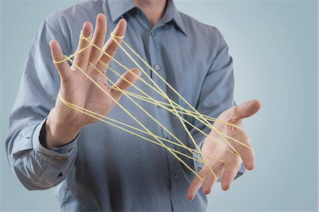 Mid section view of a man's hands making a cats cradle with string, Bavaria, Germany Stock Photo - Premium Royalty-Free, Code: 6121-08106839